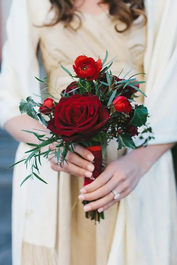 a chic red wedding bouquet of blooms and foliage is all you need for a stylish Christmas wedding