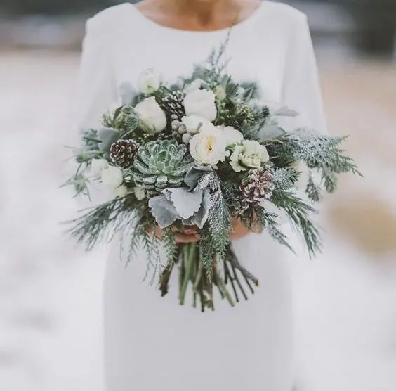 a grey and cream wedding bouquet with pale succulents, evergreens and pinecones for winter