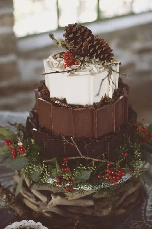a woodland-inspired Christmas wedding cake with dark, milk and white chocolate topped with berries, twigs and pinecones