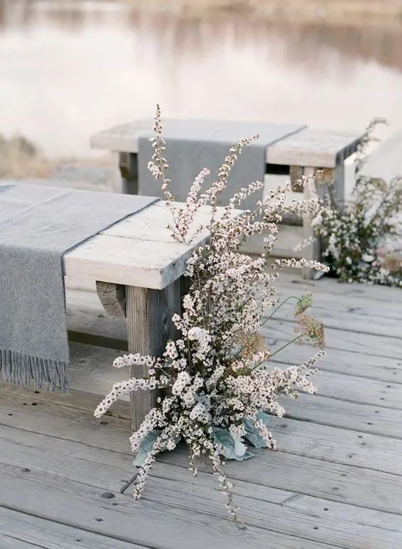 grey fringe throws on the benches plus white blooms for wedding aisle decor, so frozen-like