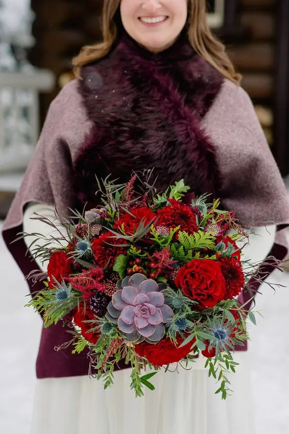 a luxurious and bright wedding bouquet with red blooms, berries, thistles, colorful succulents and greenery