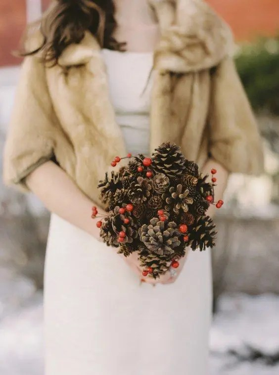 a simple Christmas wedding bouquet of pinecones and holly berries is a budget-friendly idea