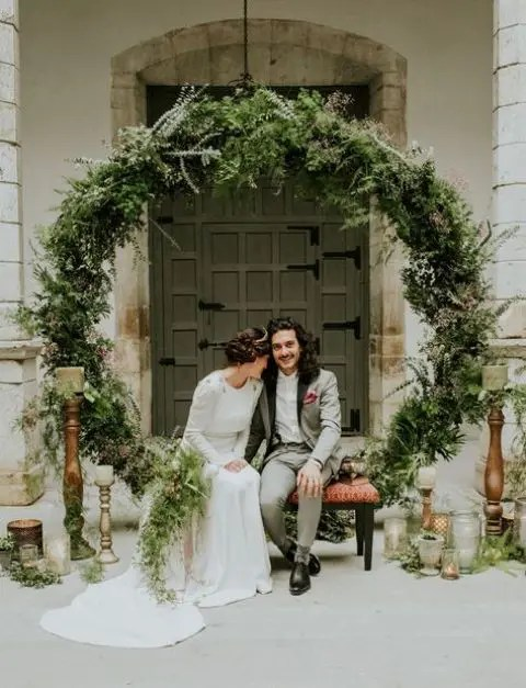 a trendy wedding backdrop of an oversized greenery wreath and lots of candles around