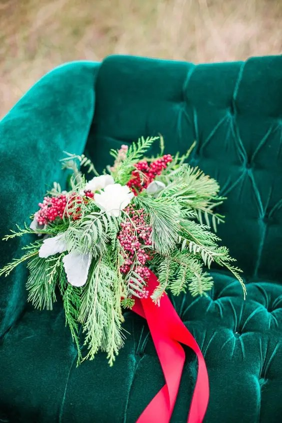 a textural wedding bouquet of evergreens, white blooms and berries plus red ribbons