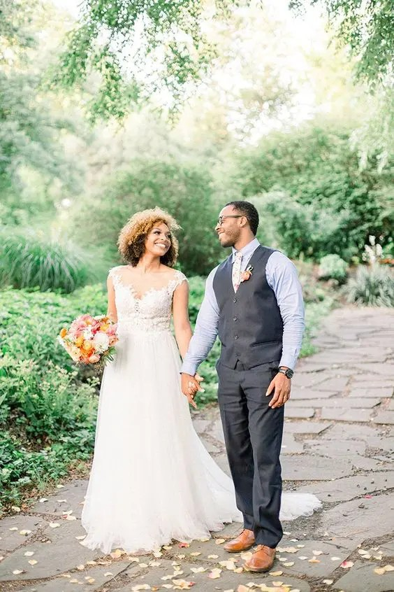 a romantic bridal gown with a lace illusion bodice, a layered skirt, the groom wearing a waistcoat and pants plus a floral tie