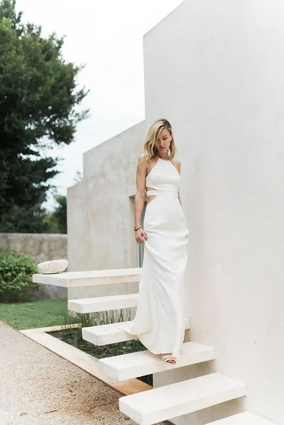 a halter neckline wedding dress with side cutouts and a strappy back, simple accessories and loose hair