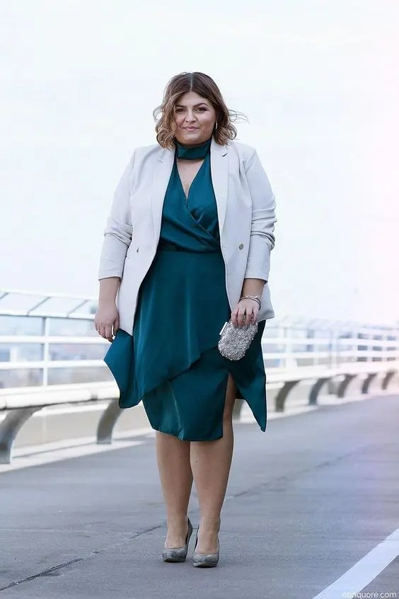 a dark green wrap midi dress with an asymmetrical skirt, a white blazer, a metallic clutch and shoes