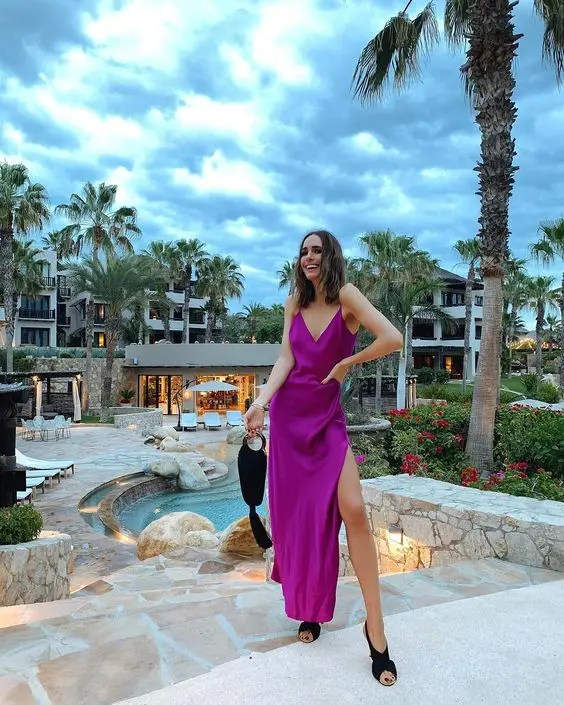 a hot purple silk maxi dress with a side slit, black criss cross shoes and a black bag with a tassel