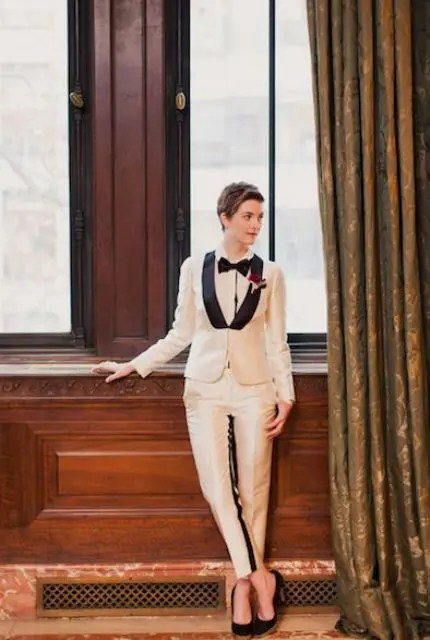 an elegant creamy tuxedo with black lapels, a white shirt and a black bow tie plus black heels is a stylish statement