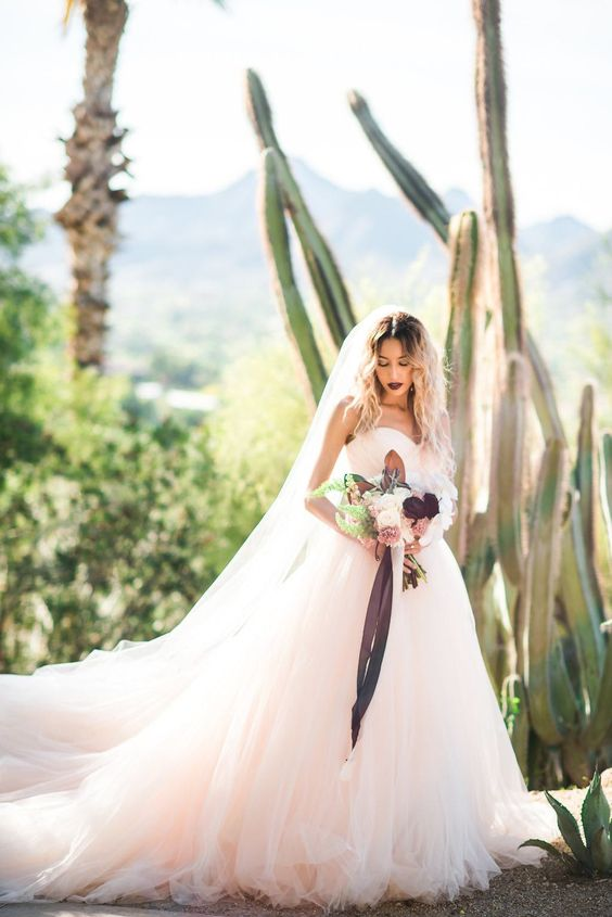 a blush strapless ballgown with a long train and a layered skirt for a dreamy look