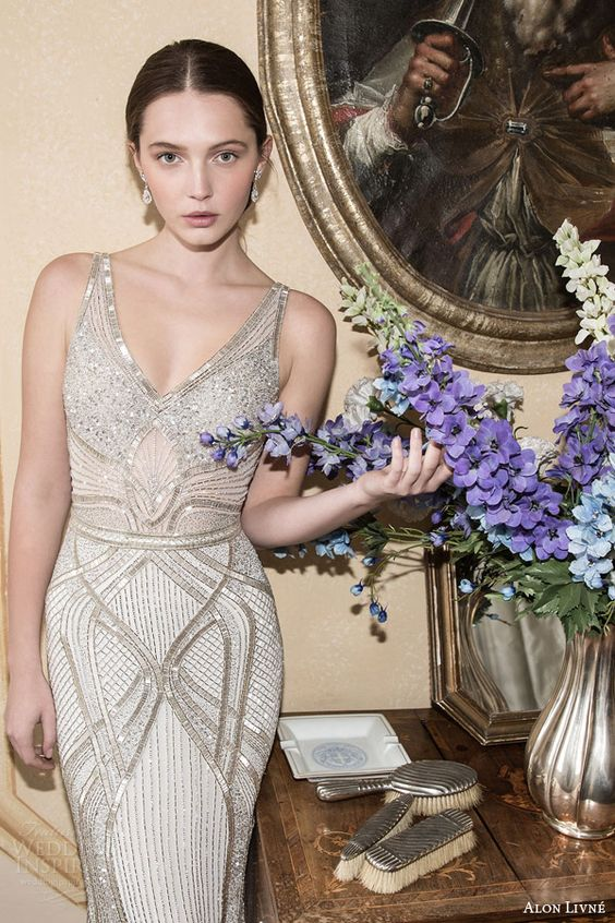 a breathtaking sheath wedding gown with geometric patterns and heavy embellishments, no sleeves and a V-neckline