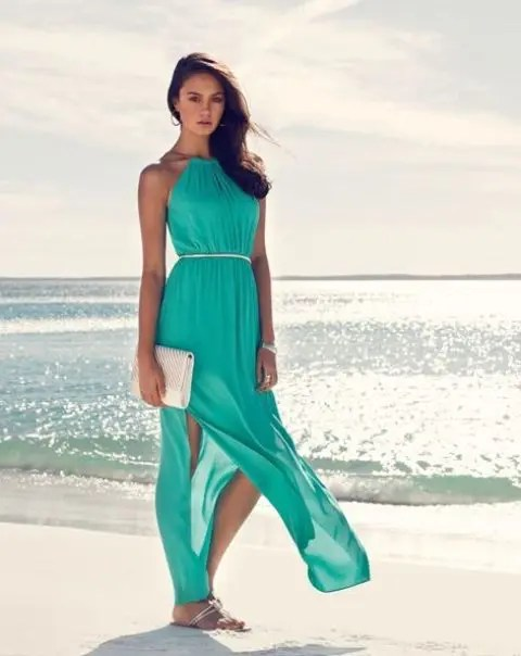 turquoise maxi dress with a halter neckline, side slits, sandals and a small white clutch