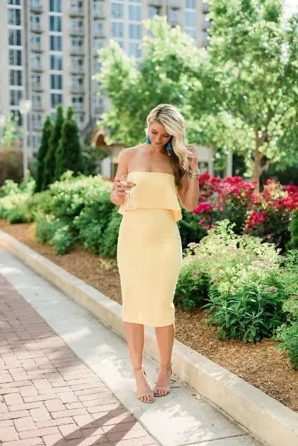 a sunny yellow strapless midi dress plus nude heeled sandals and turquoise tassel earrings
