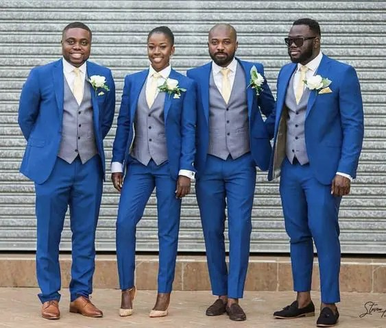 the whole party wearing bold blue suits with grey waistcoats, beige ties and white shirts and heels for the girl