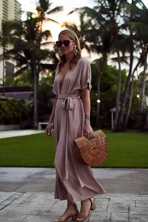 a blush maxi dress with short sleeves, a plunging neckline and a sash, a wooden bag and nude heels