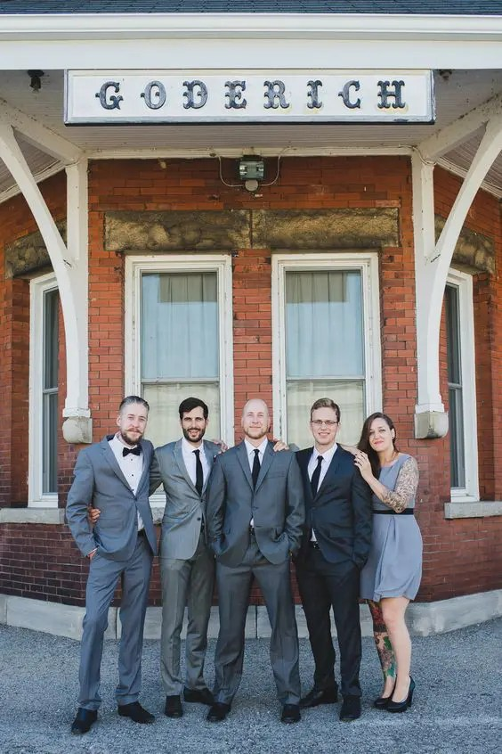 groomsmen wearign grey suits and a groomswoman rocking a grey dress and black heels