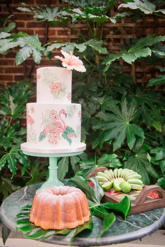 a beautiful handpainted flamingo wedding cake for a tropical wedding topped with a fresh bloom