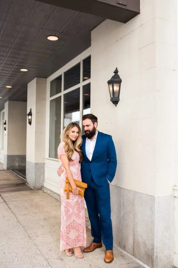a pink printed maxi dress with short sleeves, nude shoes and a mustard clutch to match his shoes