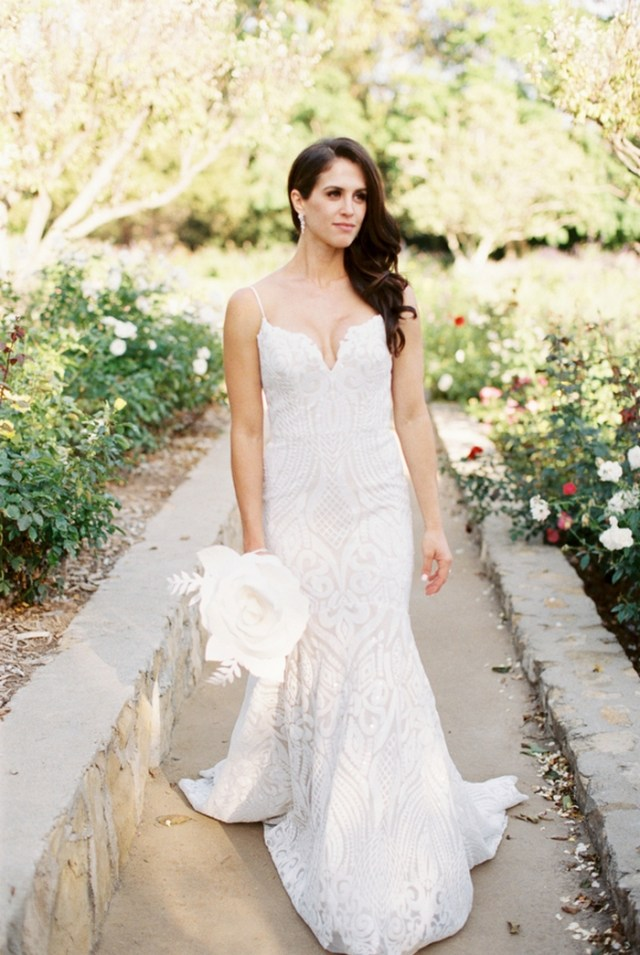 a sexy white lace sheath wedding dress with spaghetti straps and a plunging neckline