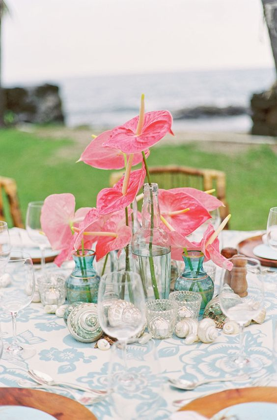 a beachy wedding centerpiece of bright pink anthuriums in blue vases and of seashells
