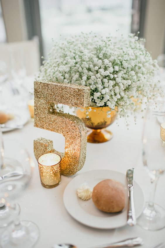 a gold bowl with baby's breath and a gold glitter table number is a chic and elegant setup