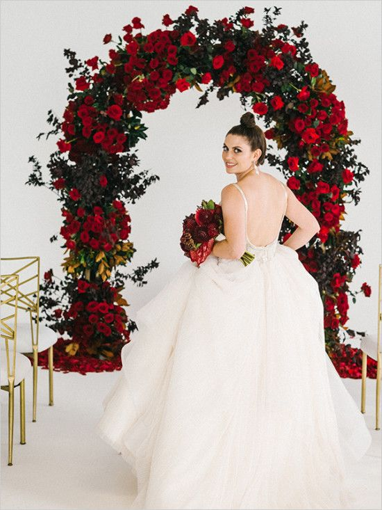 a lush red rose wedding arch with much greenery is a luxurious idea that always works