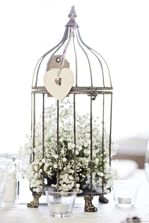 a vintage bird cage wedding centerpiece filled with baby's breath is a refined idea