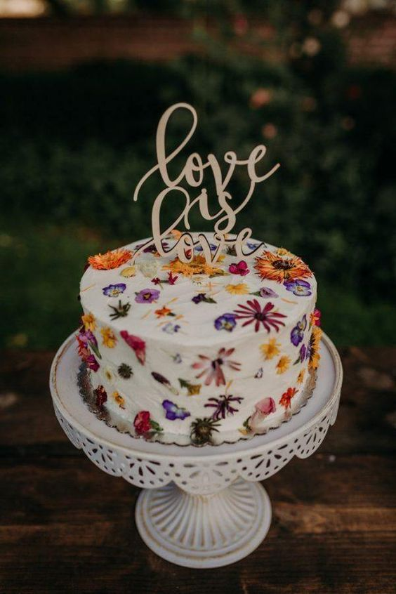 a beautiful wedding cake with edible fwildflowers in the icing and a calligraphy cake topper