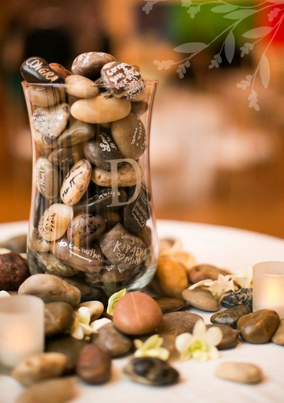 a rustic wedding guest book - lots of pebbles gathered by the couple and signed by the guests