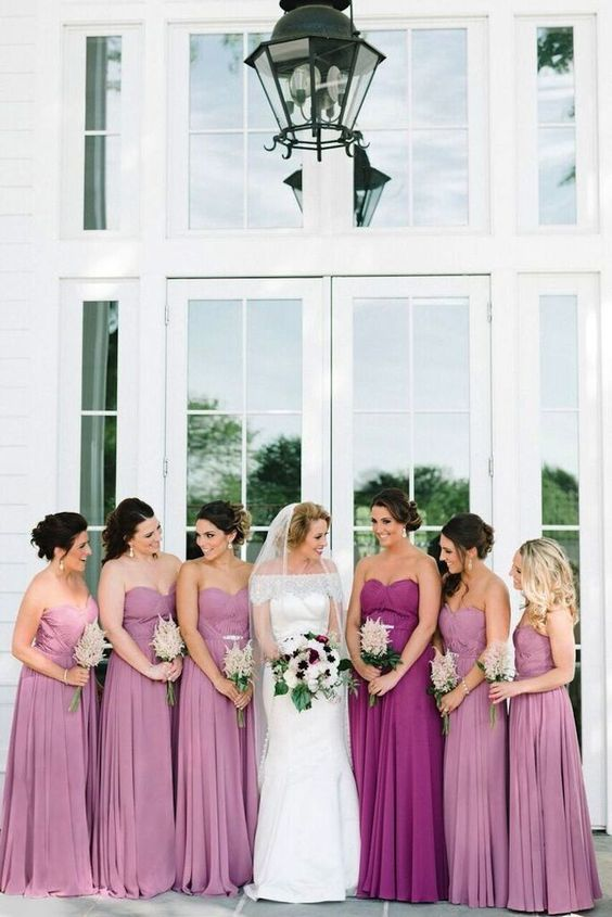 pink strapless maxi dress with pleated skirts and a purple matching gown for the maid of honor