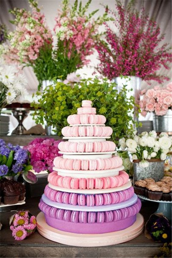 a large ombre macaron tower from pink to purple is a hot idea for a modern wedding