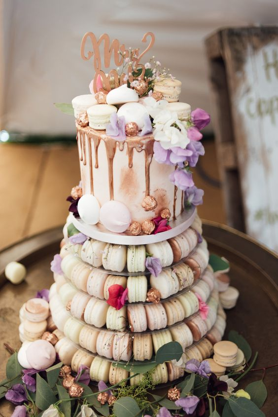 a macaron tower combined with a wedding cake topped with macarons and chocolate drip plus a topper
