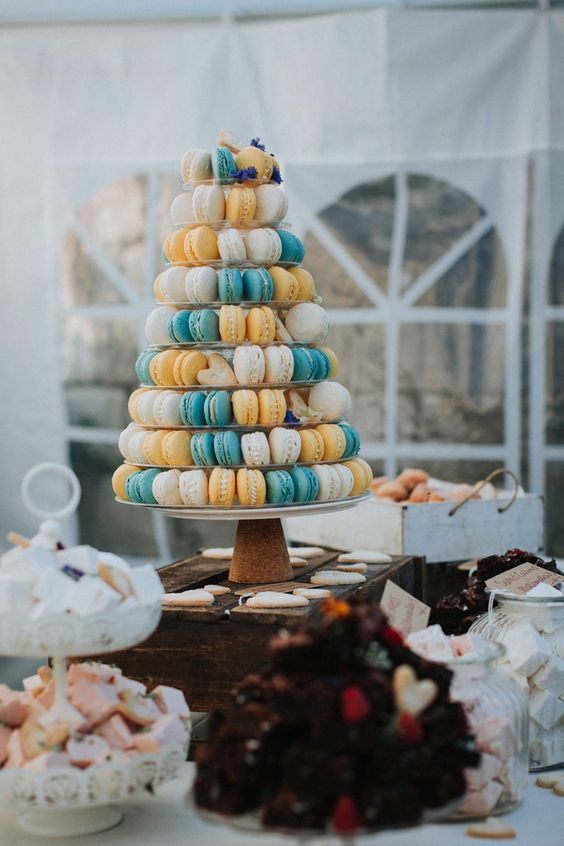 a colorful macaron and heart-shaped cookie tower with fresh blooms for decor