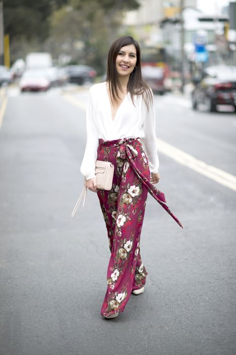 purple floral wideleg pants, a white blouse, a white bag and white heels are great for a summer wedding guest look