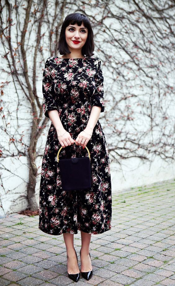 a black midi floral dress with short sleeves, black heels and a black bag with a gold handle