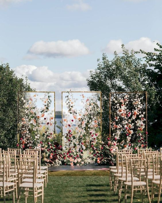 a modern bright floral wedding installation with three sheer walls and soem greenery is a gorgeous wedding backdrop