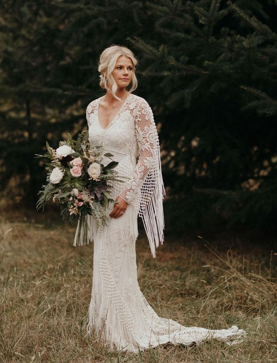 a boho lace sheath wedding gown with a V-necckline, a train and fringe on the sleeves