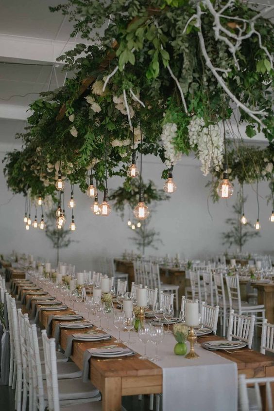 a lush greenery and white bloom installation with bulbs hanging down is a bold modenr decor idea