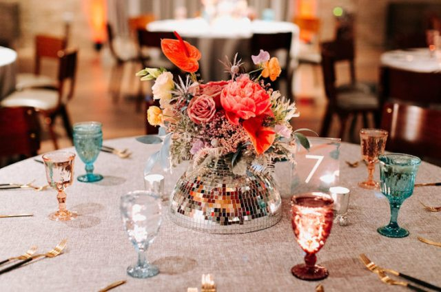 The wedding tablescape was done with various glasses, a disco ball centerpiece and bright blooms