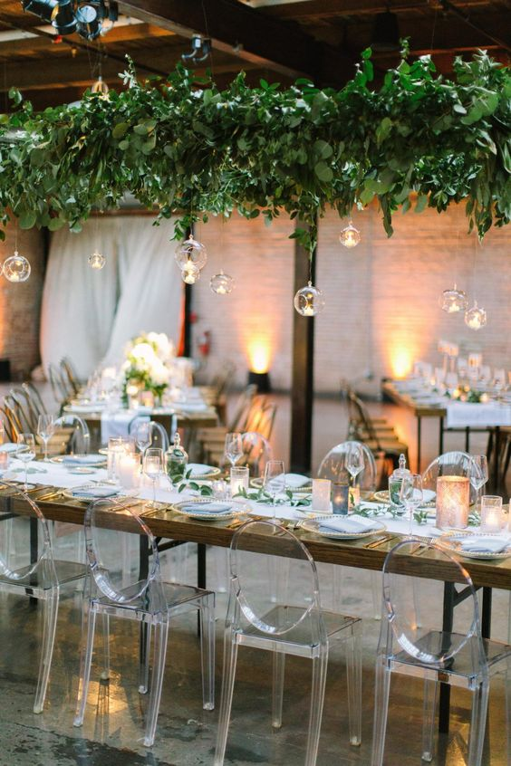 a lush greenery installation with hanging bubbles and candles is a very refreshing idea for an indoor wedding