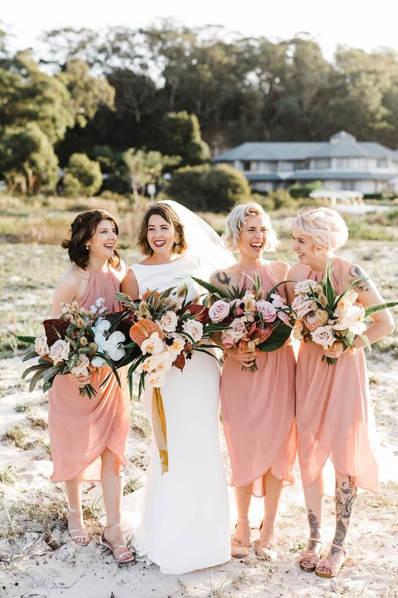 matching light pink midi wrap bridesmaid dresses with drapery and comfy sandals for a tropical wedding