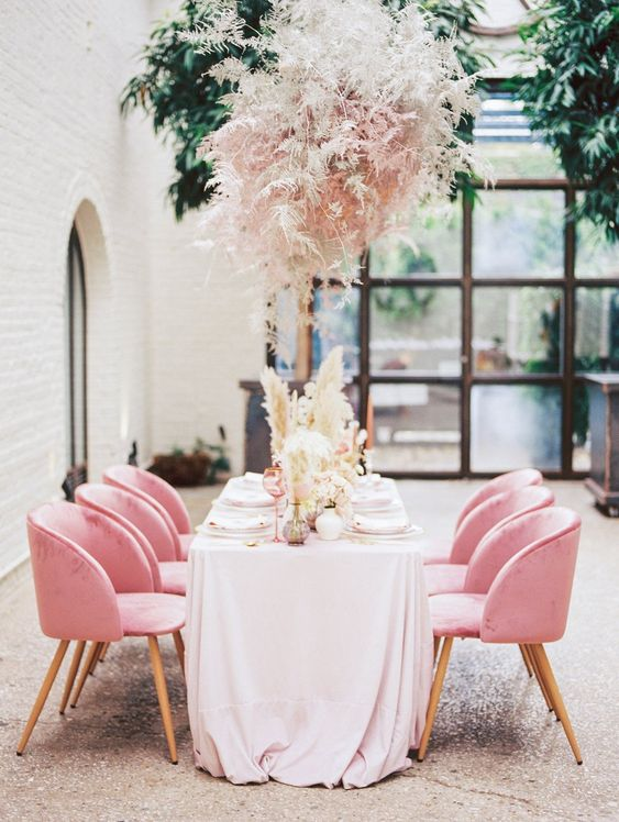 a pink grass overhead centerpiece and matching pink chair make the reception space very romantic