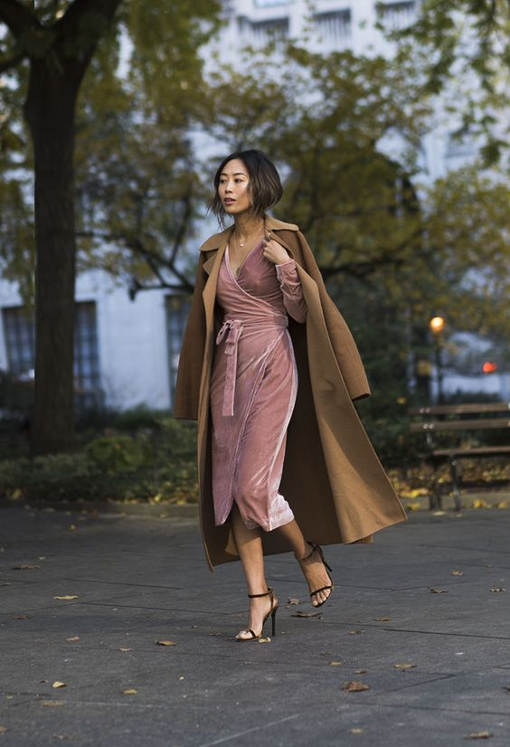 a pink wrap velvet dress with long sleeves and a V-neckline, black heels and a camel coat