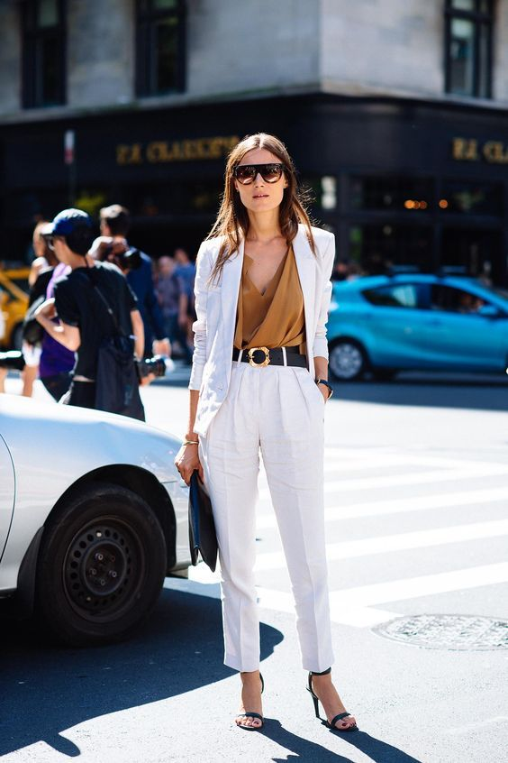 a pure white pantsuit with an oversized blazer, teal heels, a teal bag, a camel draped top