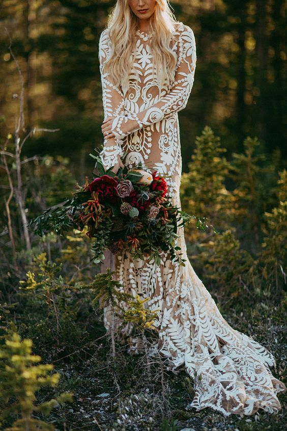 a nude boho wedding dress with long sleeves, a high nekcline, a train plus white lace all over