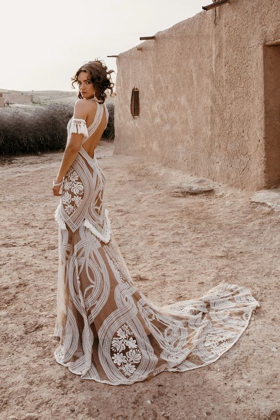 a nude wedding dress that incorporates tassel arm bands, tassles on the skirt and white lace