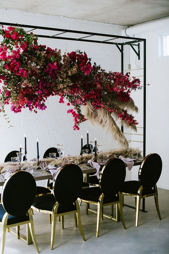 a suspended bougainvillea floral and pampas grass overhead centerpiece for a modern chic wedding reception