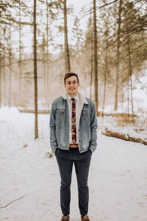 grey pants, amber boots, a white shirt, a floral tie and a denim jacket with faux fur for a relaxed woodland wedding