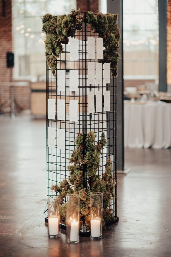a modern wedding seating chart with moss, greenery and candles around is a stylish installation