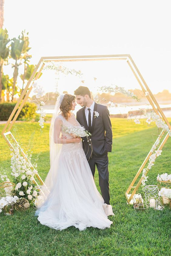 a beautiful hex spring wedding arch with white blooms, candles and geometric hangings with white florals